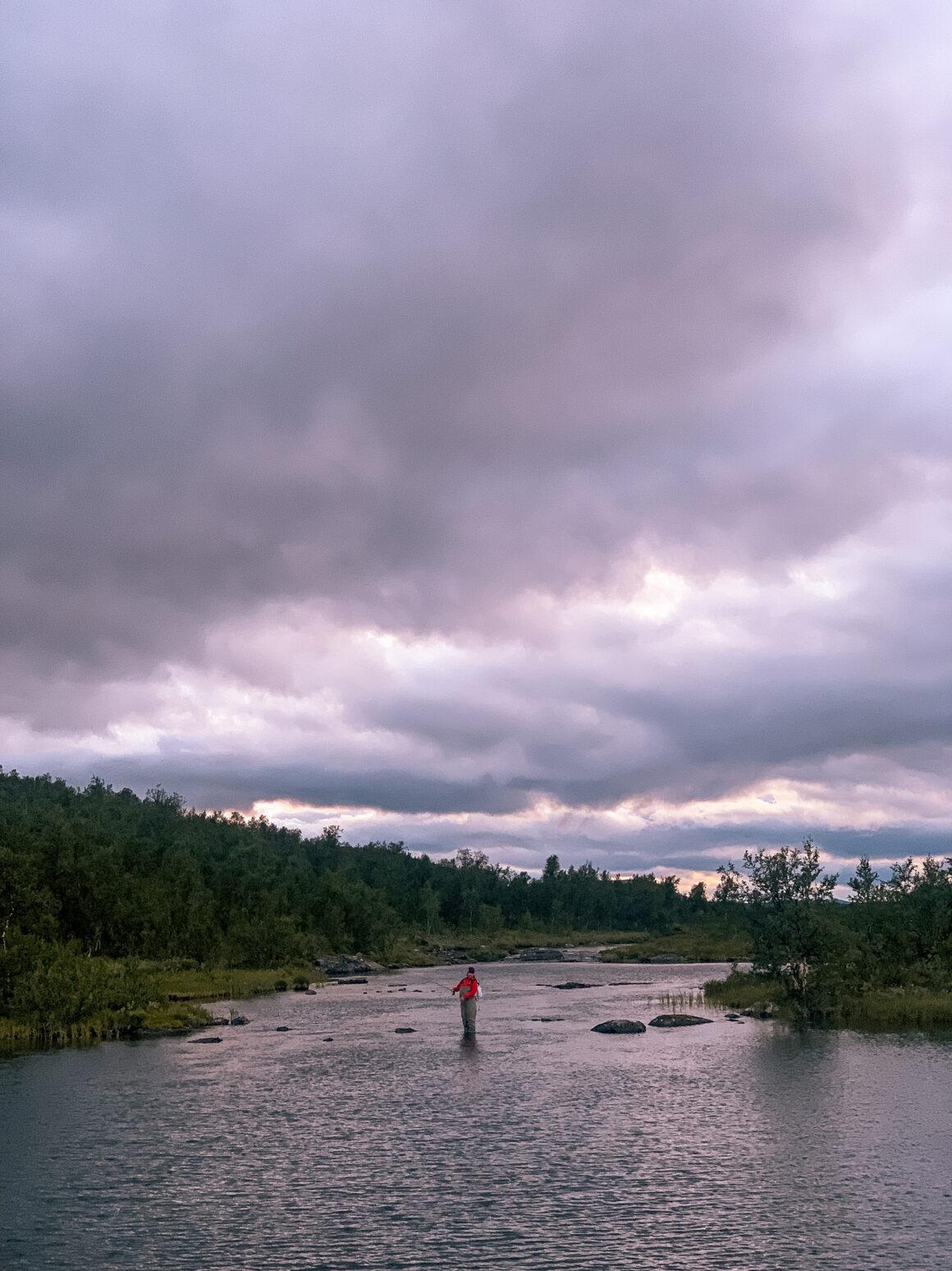 tjej som flugfiskar i vatten i lappland